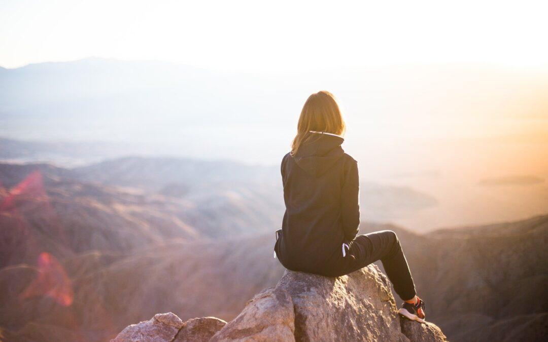 Frau auf Felsgipfel mit Blick über die Landschaft.
